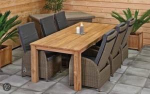 Fauteuils van vlechtwerk met een terrastafel van steigerhout.